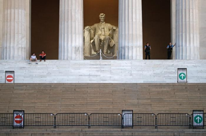 This Sunday, June 7, 2020 file photo shows visitors, left, and members of the U.S. Park Police, right, at the Lincoln Memorial as sunrise nears in Washington, the morning after massive protests over the death of George Floyd, who died after being restrained by Minneapolis police officers. On Friday, June 12, 2020