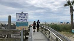 A sign in Myrtle Beach, S.C., Thursday, June 18, 2020, asks people to maintain social distancing on the beach
