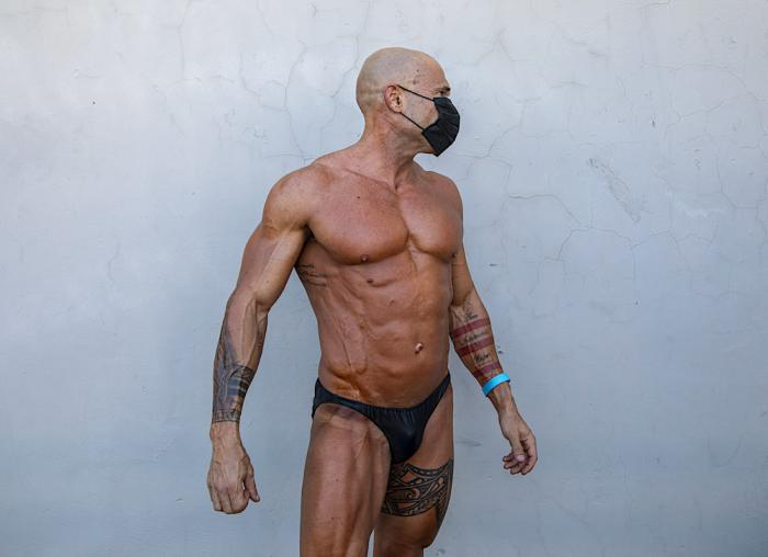 A contestant wearing protective face mask exercises backstage during the National Amateur Body Builders Association competition in Tel Aviv, Israel, Wednesday, Aug. 19, 2020.