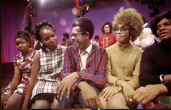 On the set of 'Soul!,' host Ellils Haizlip (middle) is surrounded by members of the J.C. White Singers after their moving performance in a scene from 'Mr. Soul!,' a film by Melissa Haizlip