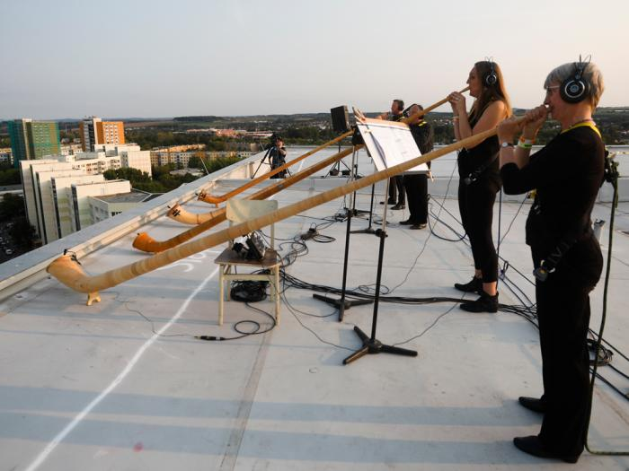 A musician with alp horns perform on the roof of an apartment block for a concert featuring distant harmonies, at a time when cultural events have been disrupted by the coronavirus pandemic, in the Prohlis neighborhood in Dresden, Germany, Saturday, Sept. 12, 2020
