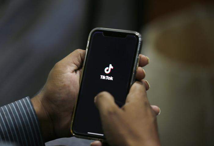 In this July 21, 2020 file photo, a man opens social media app 'TikTok' on his cell phone, in Islamabad, Pakistan.