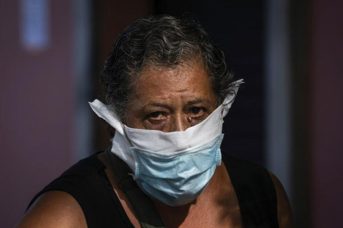 A woman wearing a face mask to prevent the spread of the coronavirus walks in the southern neighbourhood of Vallecas in Madrid, Spain.