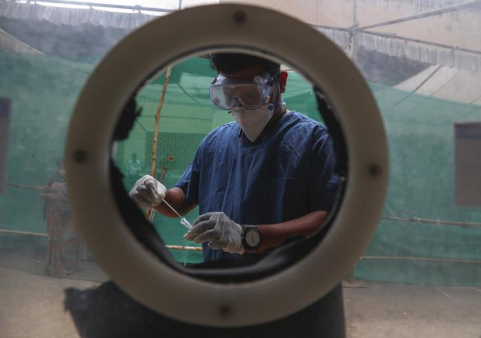 A  health worker collects nasal swab samples at a COVID-19 testing center in Hyderabad, India.