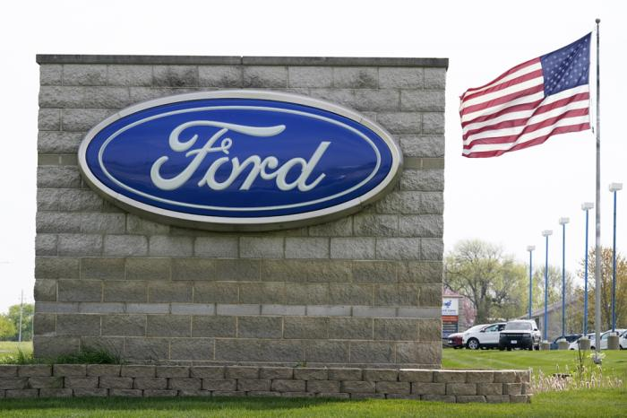 In this April 27, 2021 file photo, an American flag flies over a Ford auto dealership, in Waukee, Iowa