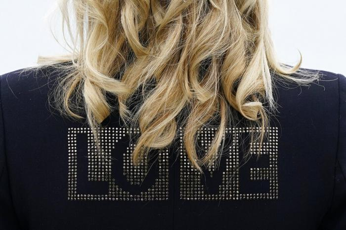 """First lady Jill Biden turns around to show the word """"love"""" on the back of her jacket as she speaks with reporters after visiting with Carrie Johnson, wife of British Prime Minister Boris Johnson, ahead of the G-7 summit."""