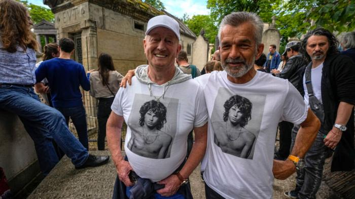 Fred Verheijden, left, and Hans van Schie of the Netherland wear shirts with the picture of late rock singer Jim Morrison at the Pere-Lachaise cemetery in Paris, Saturday, July 3, 2021. Fans across Europe gathered at the grave of rock legend Jim Morrison to mark the 50th anniversary of his death.(AP Photo/Michel Euler)