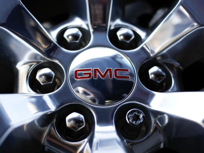 In this April 25, 2017 file, photo, a GMC logo is displayed on the wheel of a truck at a General Motors dealer's lot in Nashville, Tenn.