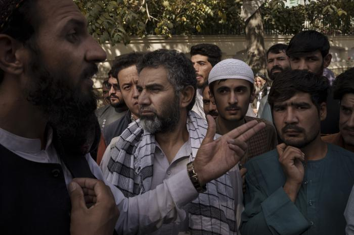 A member of the Taliban, left, talks to Afghans gathering outside a government passport office recently re-opened after Taliban announced they would be issuing a backlog of applications approved by the previous administration in Kabul, Afghanistan, Wednesday, Oct. 6, 2021.